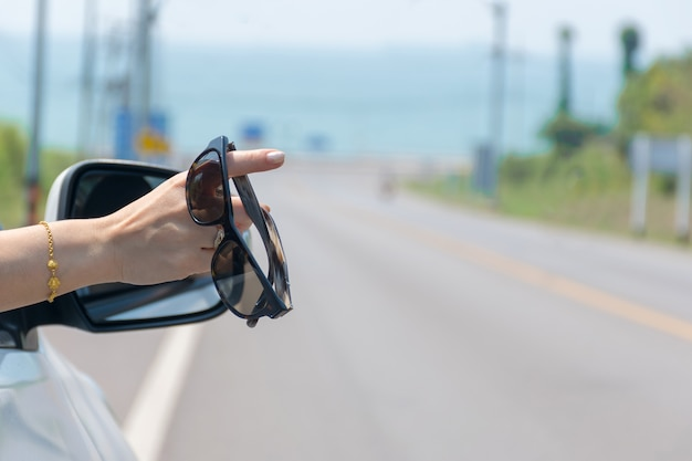 Handheld glasses are in the car travel summer sea and beach
