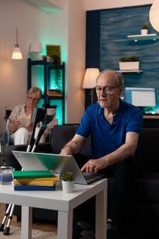 핸디캡 은퇴한 사람들은 기술과 의료 장비를 갖춘 현대적인 집에서 휴식을 취합니다. 목발과 휠체어에 여자와 소파에 앉아 디지털 노트북 컴퓨터 장치를 사용하는 노인