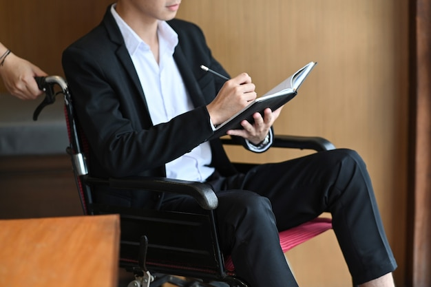 Handicapped businessman in wheelchair holding pen and writing some information on notebook.