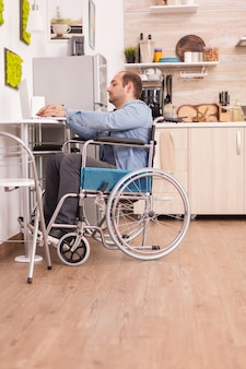 Handicapped businessman in wheelchair using laptop in kitchen. disabled paralyzed handicapped man with walking disability integrating after an accident.
