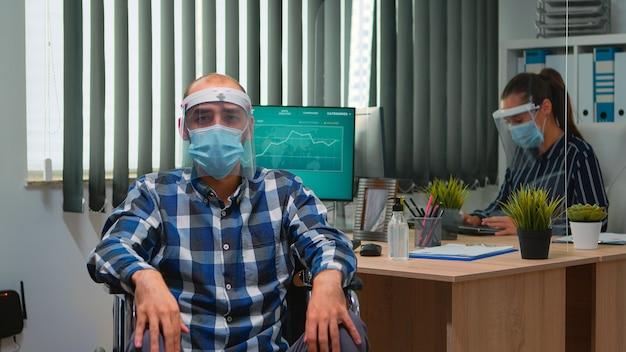 Uomo d'affari disabile in sedia a rotelle con maschera che tiene una conferenza online in ufficio durante la pandemia di covid-19. libero professionista immobilizzato che lavora in società finanziaria nel rispetto della distanza sociale.