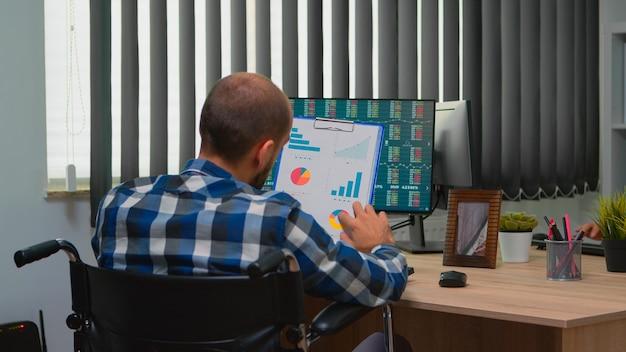ビルのオフィスの机の上の車椅子に固定されて座っているグラフをチェックする財務統計を扱う障害のあるビジネスマン。最新のテクノロジーとドキュメントを使用した麻痺したフリーレーサー。