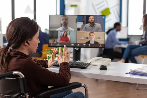 Handicapped businesswoman in wheelchair having online videocall meeting conference