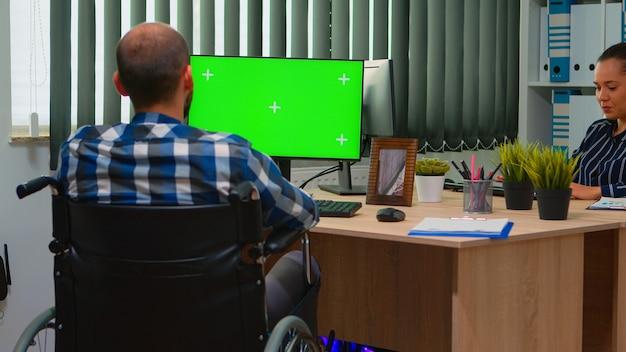 同僚と話している緑色の画面でpcを見ている障害者の障害者フリーランサー。クロマキー、モックアップ、ビデオ会議用のグリーンスクリーンを備えたコンピューターを使用して車椅子に固定されたビジネスマン。