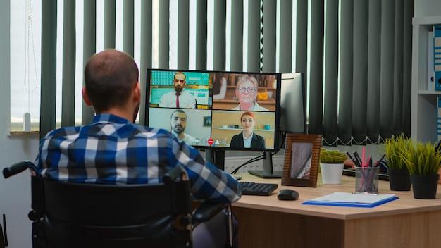 営業所でオンライン会議を行っているビデオ通話中に車椅子で話している障害者の障害者マネージャー。麻痺した、固定化されたフリーランサーが、最新のテクノロジーを使用して金融会社で働いています。