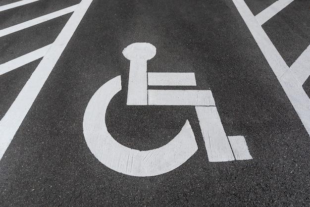 道路アスファルトに塗装された身体障害者/障害者用駐車場標識。