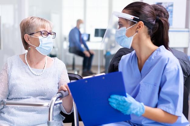 病院の待合室で専門医と話し合う歩行フレームの障害のある年配の女性