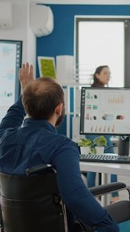 Предприниматель с ограниченными физическими возможностями приходит в офис приветствуя коллег