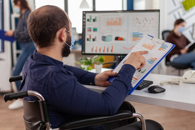 Handicapped entrepreneur with protective face mask working in new normal business financial company checking project documents