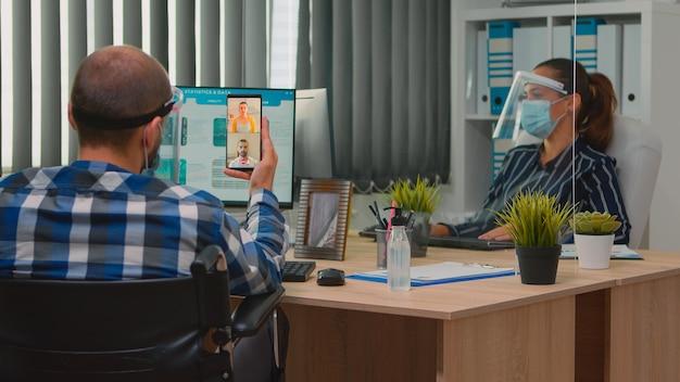 Esperto finanziario disabile in sedia a rotelle che parla in webcam con cowerkers a distanza durante il coronavirus in compagnia con il nuovo normale ufficio commerciale. imprenditore immobilizzato nel rispetto della distanza sociale.