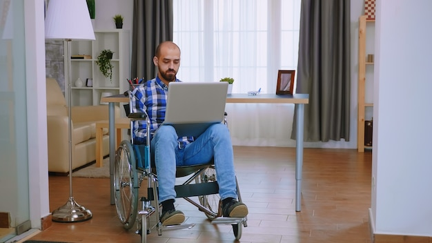 Handicapped freelancer in wheelchair working on laptop.