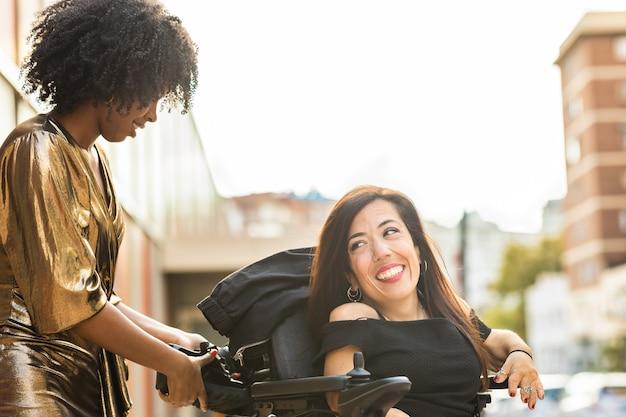모터 휠체어를 탄 장애인 히스패닉 여성은 친구들과 함께 새해 전야 파티를 축하합니다