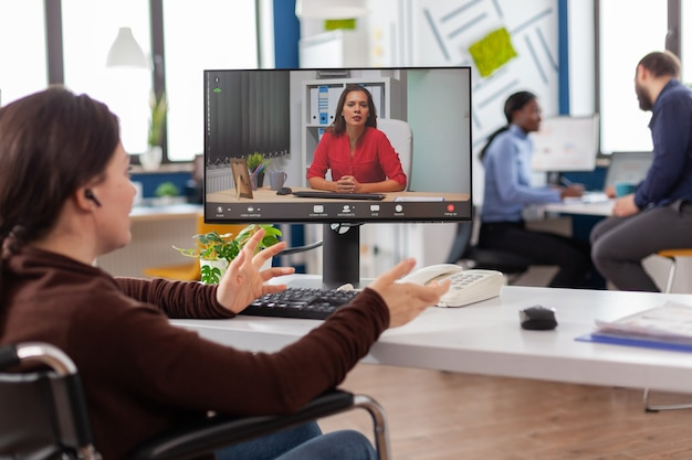 Handicapped invalid immobilized business woman talking about sale report in video conference working overtime in start-up office