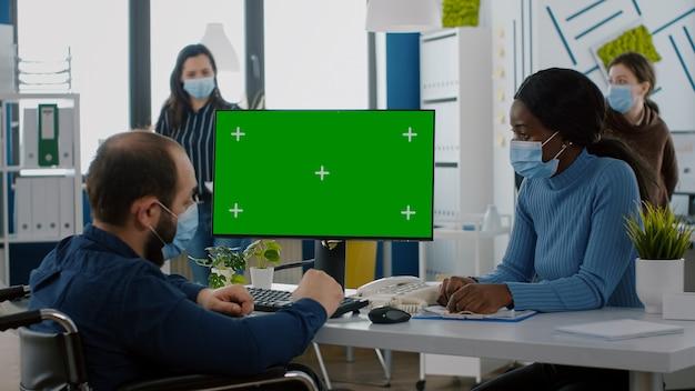 휠체어에 앉아 녹색 바탕 화면을 보고 있는 보호 마스크를 쓴 장애를 가진 무효 관리자...