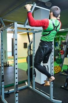 Handicapped man doing pull-ups in gym