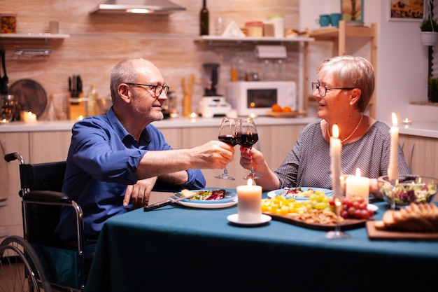 Handicapped man having dinner with man in kitchen toasting. wheelchair immobilized paralyzed handicapped man dining with wife at home, enjoying the meal