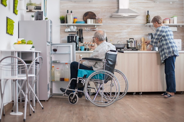 Handicapped man helping wife at the kitchen by taking eggs carton from refrigerator. senior woman helping handicapped husband. living with disabled person with walking disabilities