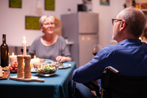 축제 저녁 식사 중에 휠체어에 앉아 우는 잔을 들고 장애인 남자. 행복한 노인 부부는 아늑한 주방에서 함께 식사를 하고 식사를 즐기고 기념일을 축하합니다