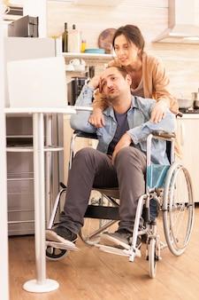 キッチンのラップトップでのビデオ会議中に車椅子の障害者と妻。事故後に統合した歩行障害のある障害者麻痺障害者。