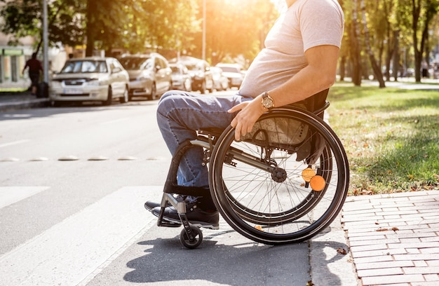 通りの道路を横断する車椅子の障害者。