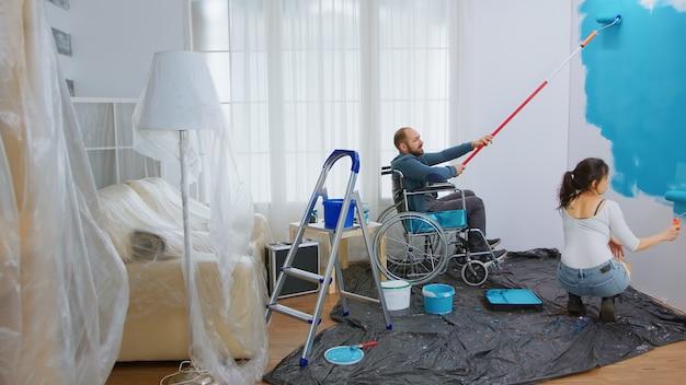 아내가 아파트 벽에 페인트칠을 하는 것을 돕는 휠체어를 탄 장애인. 장애인, 장애인 및 수리 및 즉석에서 아파트 재장식 및 주택 건설을 돕는 남자를 움직이지 못하게 합니다.