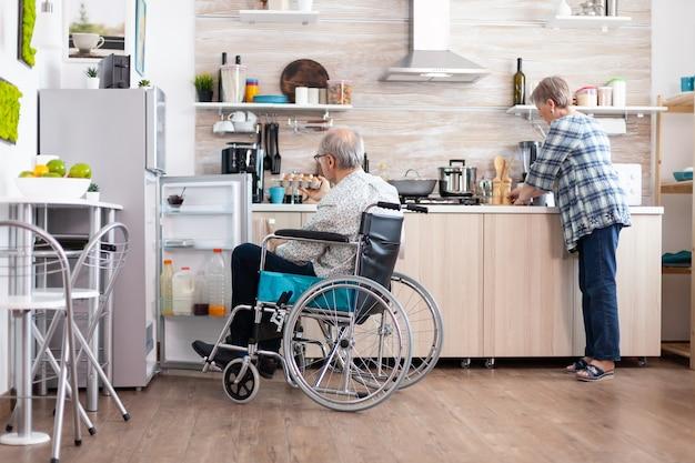 휠체어를 탄 장애인 남자는 냉장고를 열고 아내가 부엌에서 아침 식사를 준비하는 것을 돕습니다. 마비된 남편을 위해 요리하는 시니어 여성, 보행 장애가 있는 남성과 함께 생활