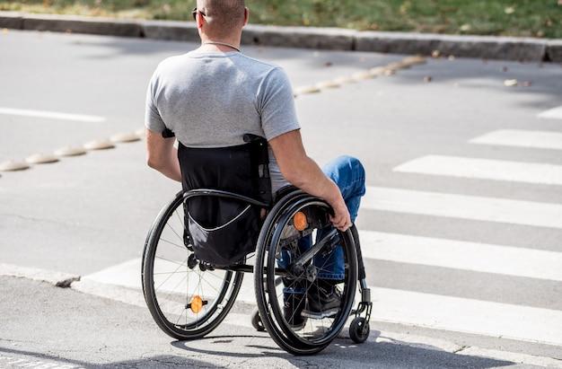 横断歩道で道路を横断する準備をしている車椅子の障害者の男性