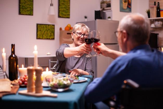 휠체어를 탄 장애인 남자가 저녁 식사 중에 아내와 함께 건배했습니다. 행복한 노인 부부는 아늑한 주방에서 함께 식사를 하고 기념일을 축하하며 식사를 즐기고 있습니다.