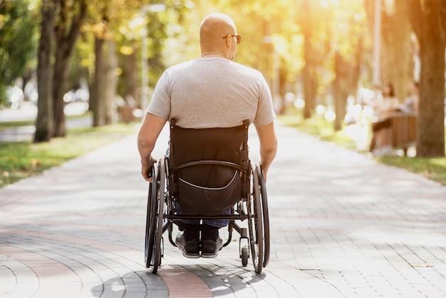 公園の路地で車椅子で歩く障害者