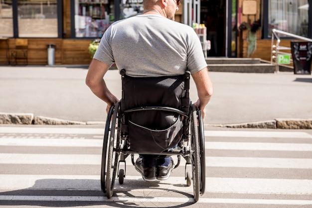 Handicapped man in wheelchair crossing street road.