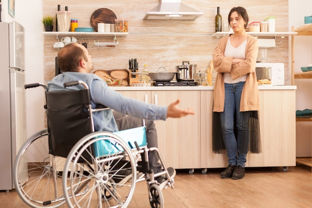 Handicapped man in wheelchair having a dispute with wife in kitchen. disabled paralyzed handicapped man with walking disability integrating after an accident.