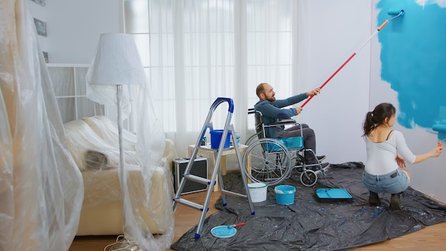 Handicapped man in wheelchair helping wife to paint apartment wall. handicapped, disabled ill and immobilizes man helping with apartment redecoration and home construction while renovating and improvi
