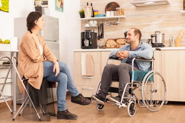 Uomo disabile in sedia a rotelle che guarda la moglie premurosa in cucina. disabile paralizzato uomo handicappato con disabilità motoria che si integra dopo un incidente.