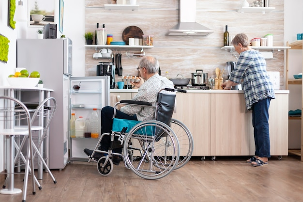 Uomo disabile in sedia a rotelle che apre il frigorifero e aiuta la moglie a preparare la colazione in cucina. donna anziana che cucina per il marito paralizzato, che vive con un uomo disabile con disabilità motorie