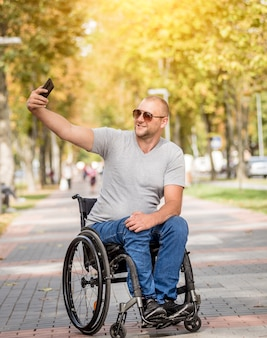 Handicapped man in wheelchair at the park alley use a smartphone
