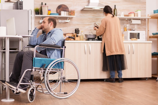 Handicapped man in wheelchair using laptop in kitchen and wife is preparing meal. disabled paralyzed handicapped man with walking disability integrating after an accident.