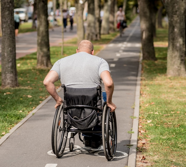 Handicapped man in wheelchair walk at the park alley.