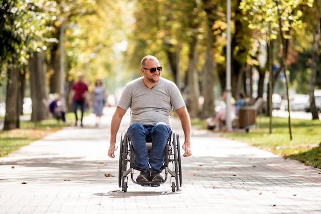 Handicapped man in wheelchair walk at the park alley Premium Photo