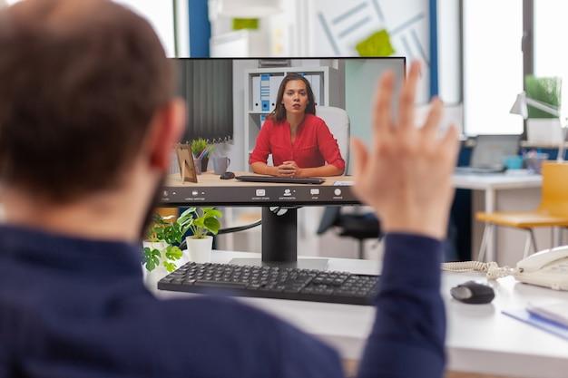 ストラテアップビジネスオフィスで働く仮想会議中にコンピューターでカメラの前に座っているチームリーダーとビデオ通話で話している障害者マネージャー