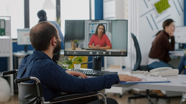 Handicapped manager talking on videocall with team leader sitting in front of camera at computer dur...