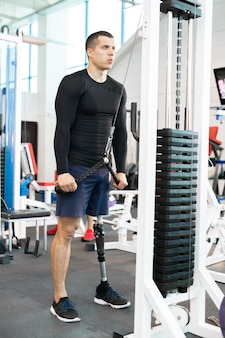 Handicapped muscular man working out using machines