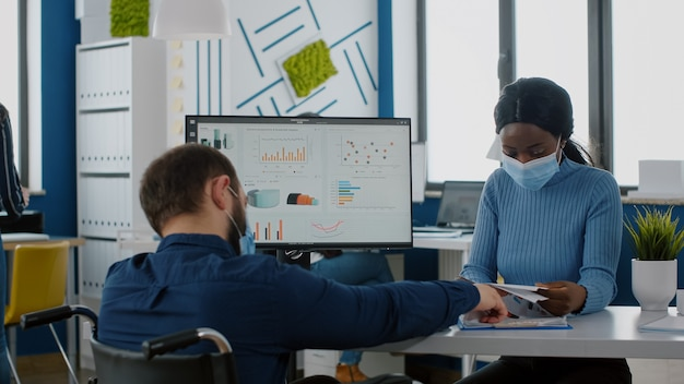 黒人の同僚の経済的戦略に説明する障害者のオフィスマネージャー