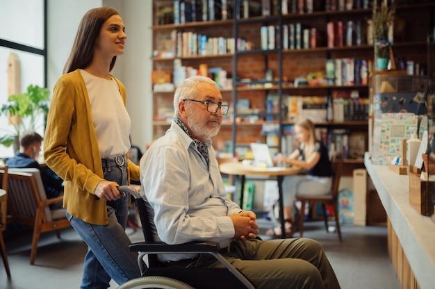 Человек пожилого возраста с ограниченными возможностями и молодой опекун