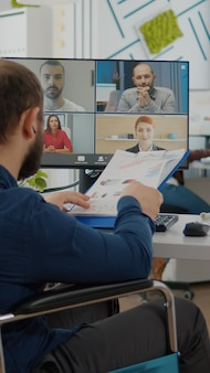 Инвалид парализованный инвалид менеджер разговаривает с командой по видеозвонку Premium Фотографии