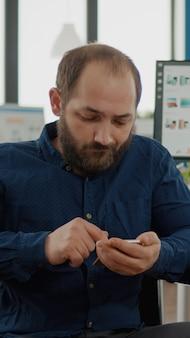 Инвалид, парализованный парализованный молодой сотрудник-инвалид, просматривающий на смартфоне во время работы набор текста, поиск, сидя в инвалидной коляске. разнообразная команда обсуждает финансовый проект, проверяет статистику
