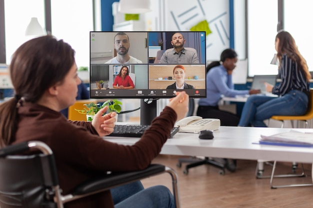 Handicapped paralyzed invalid employee during virtual meeting talking on videocall working from start up business office discussing with partners online using webcam