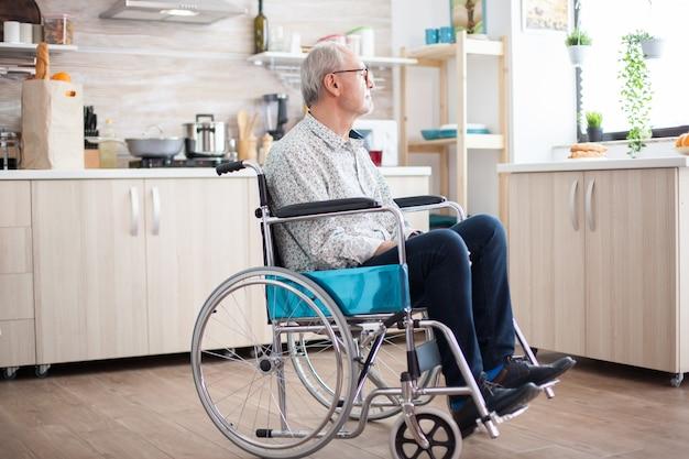 車椅子の障害者の年配の男性は、窓を見て孤独を感じています。怪我やリハビリ後の高齢者障害者年金受給者、悲しみに満ちたうつ病の無効者のための麻痺と障害、心配