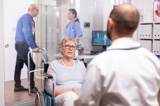 Handicapped senior patient in wheelchair talking with doctor in hospital