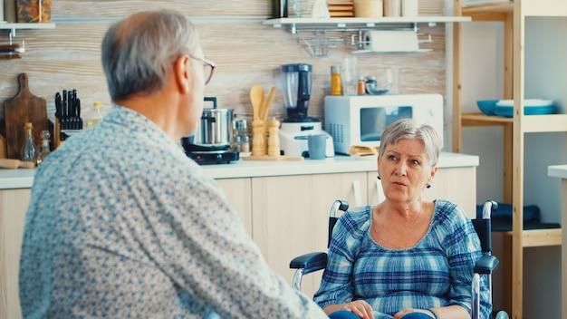 ガス炊飯器で食事の準備をしている間、夫と車椅子で結合している障害のある年配の女性。妻と会話をしている老人。歩行障害のある障害者との生活