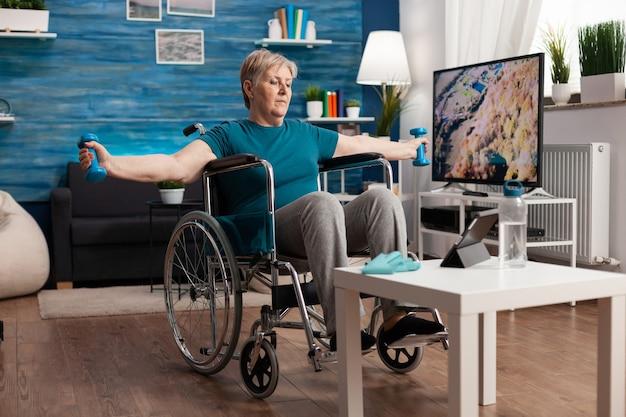 휠체어를 탄 장애인 노인 여성은 거실에서 운동 아령을 사용하여 신체 저항을 운동하는 팔 근육을 스트레칭합니다. 태블릿에서 라이프스타일 에어로빅 비디오를 보고 있는 장애인 연금 수급자